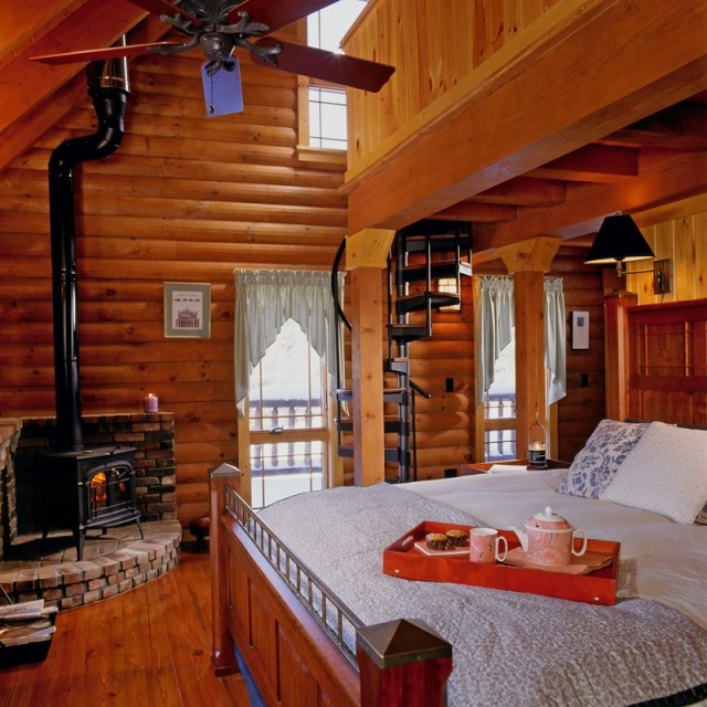 log home bedroom with wood stove and spiral staircase