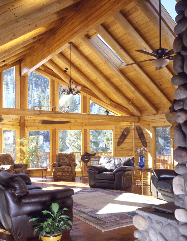 log home great room with wall of windows and leather furniture