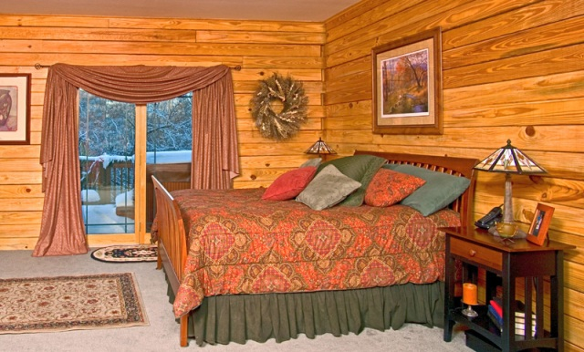 log home bedroom with jacuzzi outside