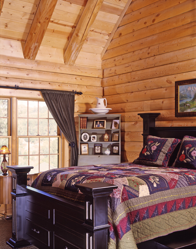 log home bedroom with black bed and quilt