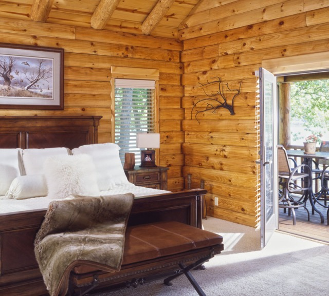 log home bedroom with french door leading to patio