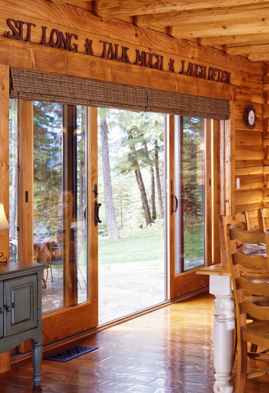 log home dining room with roman shades on sliding glass doors