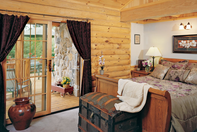 Log Home Bedroom With Sliding Glass Doors Onto Patio