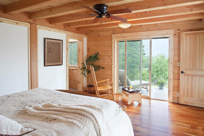 log home master bedroom with sliding patio doors