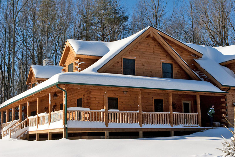 real log home covered in snow