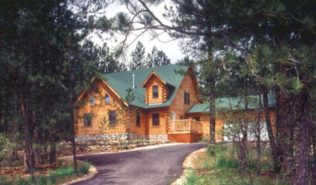 log home with green asphalt shingle roof